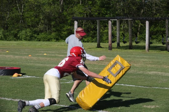 Riverdale coach Will Kriesky works on tackling drills with players during Monday's spring practice.