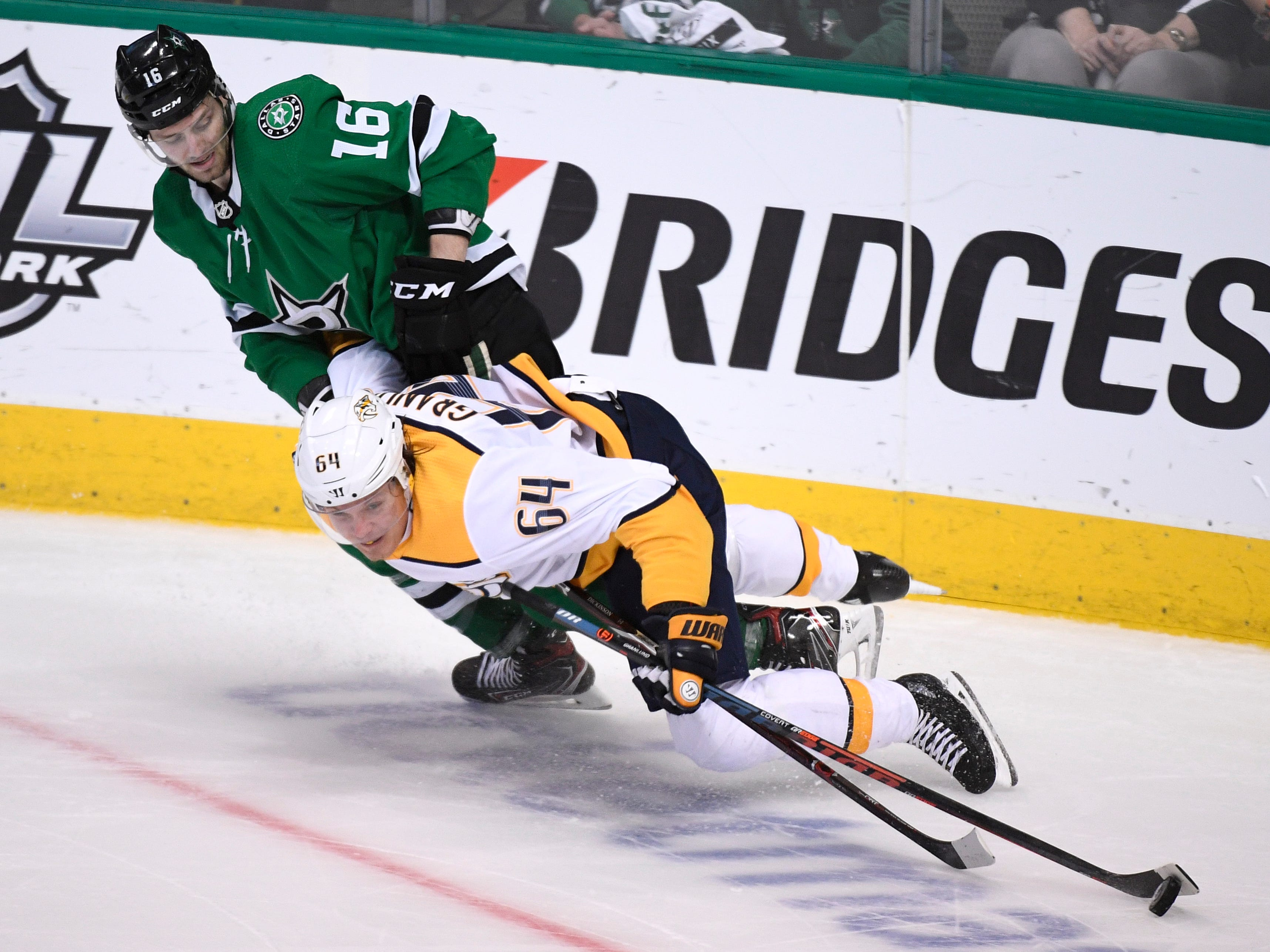 Nashville Predators center Mikael Granlund (64) moves the puck defended by Dallas Stars center Jason Dickinson (16) during the third period of the divisional semifinal game at the American Airlines Center in Dallas, Texas, Monday, April 22, 2019.