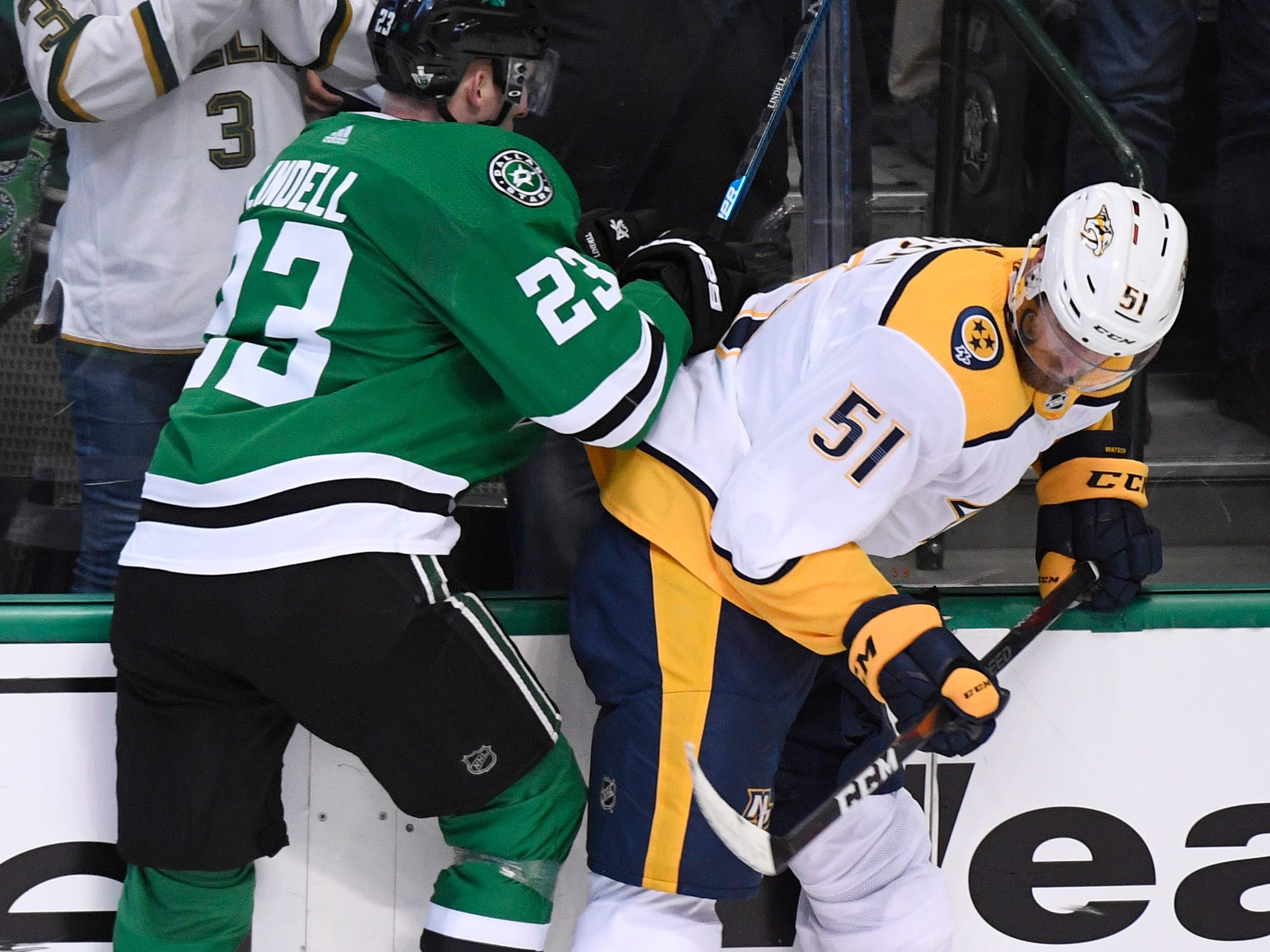 Dallas Stars defenseman Esa Lindell (23) and Nashville Predators left wing Austin Watson (51) battle along the boards during the second period of the divisional semifinal game at the American Airlines Center in Dallas, Texas, Monday, April 22, 2019.