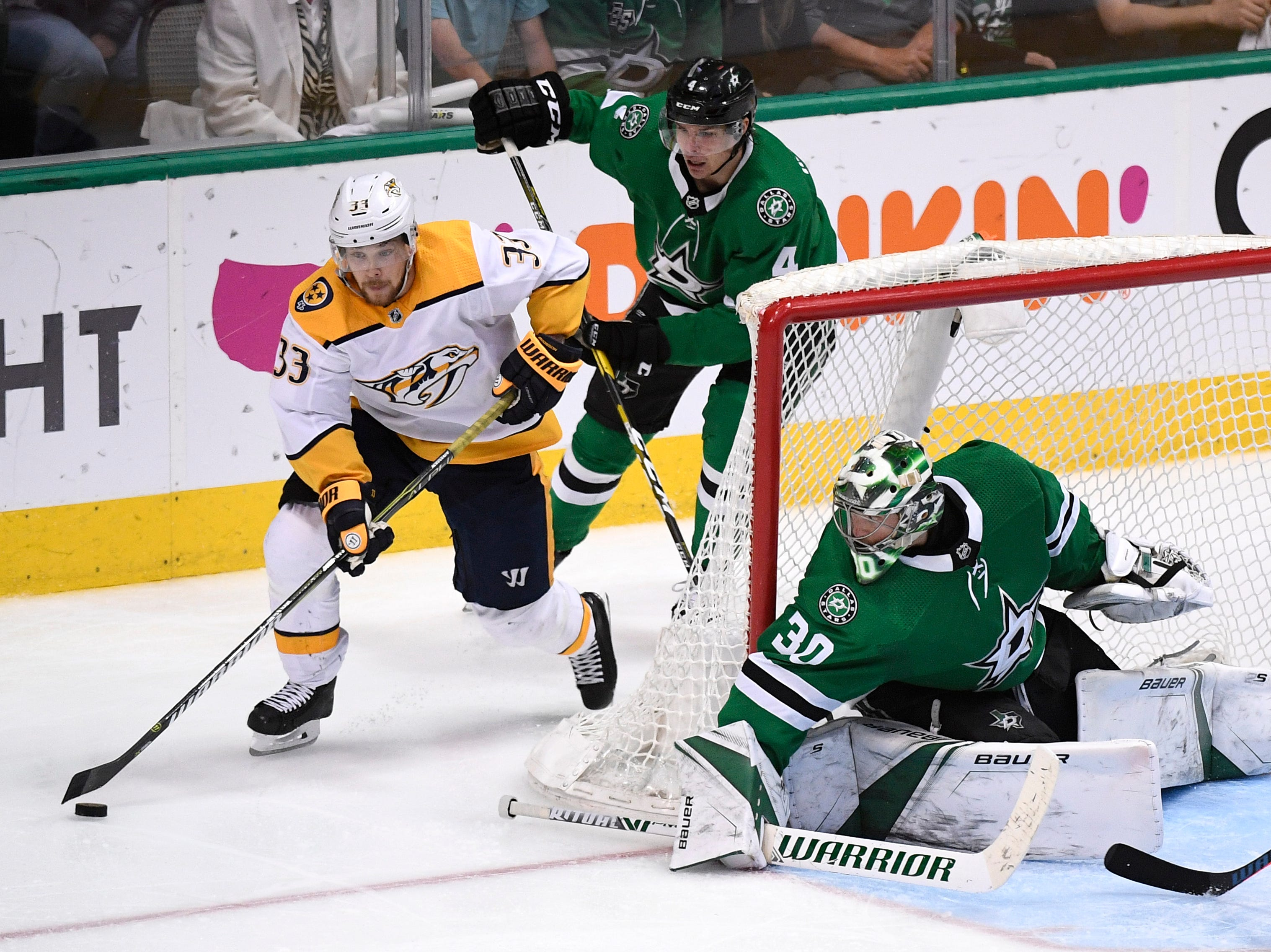Nashville Predators right wing Viktor Arvidsson (33) moves the puck behind Dallas Stars goaltender Ben Bishop (30) defended by Stars defenseman Miro Heiskanen (4) during overtime of the divisional semifinal game at the American Airlines Center in Dallas, Texas, Monday, April 22, 2019.