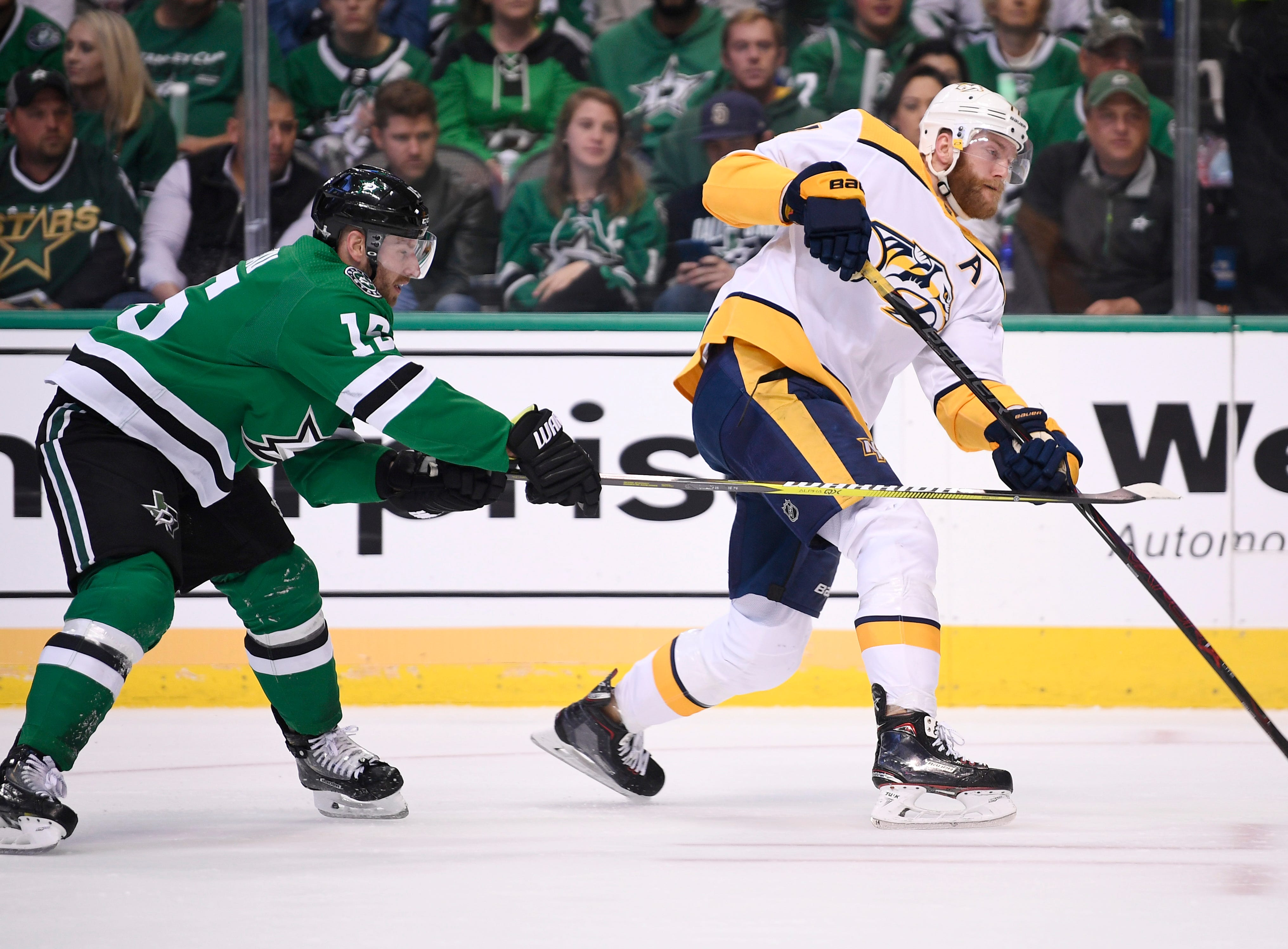 Nashville Predators defenseman Mattias Ekholm (14) takes a shot defended by Dallas Stars left wing Blake Comeau (15) during the first period of the divisional semifinal game at the American Airlines Center in Dallas, Texas, Monday, April 22, 2019.