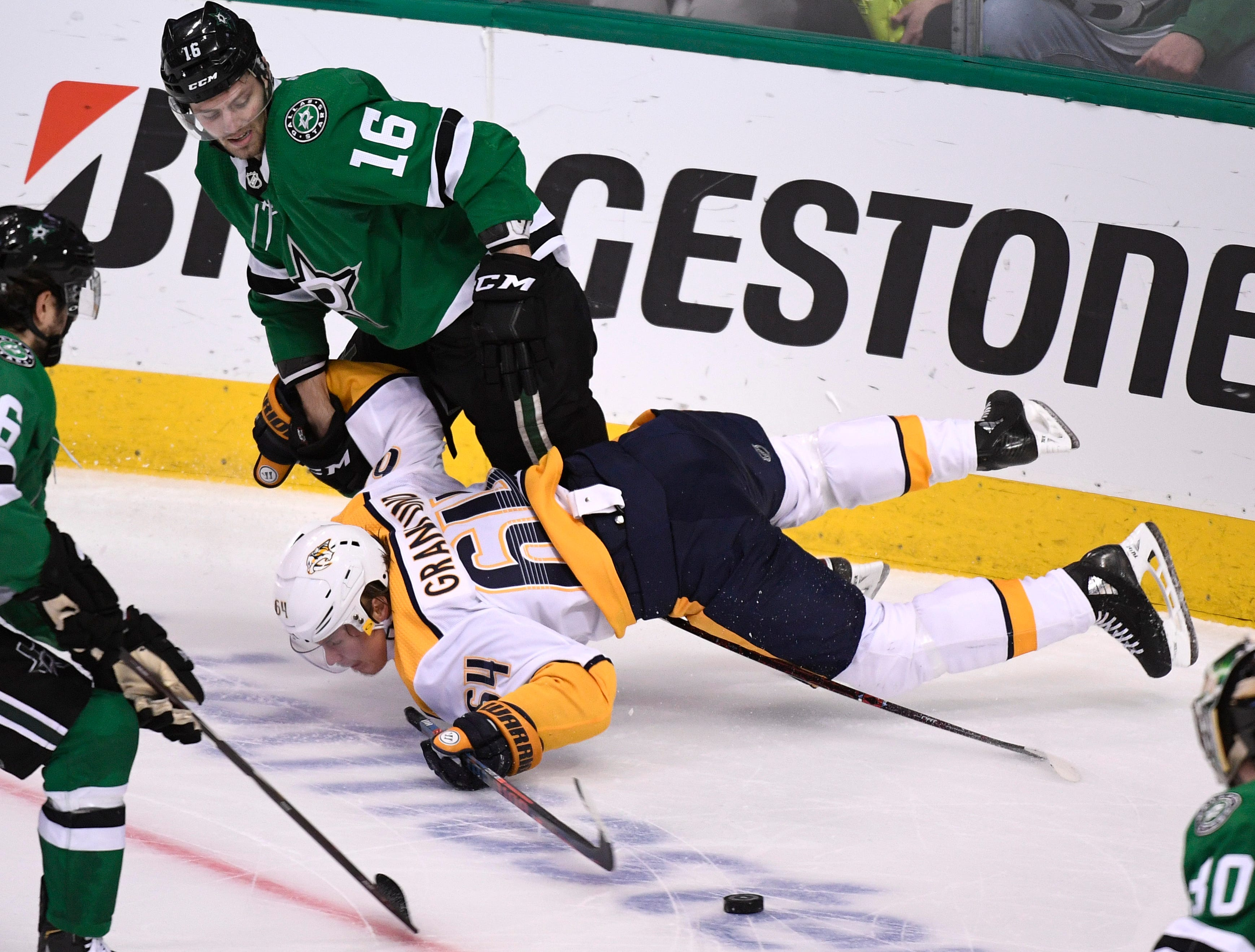 Nashville Predators center Mikael Granlund (64) hits the ice defended by Dallas Stars center Jason Dickinson (16) during the third period of the divisional semifinal game at the American Airlines Center in Dallas, Texas, Monday, April 22, 2019.