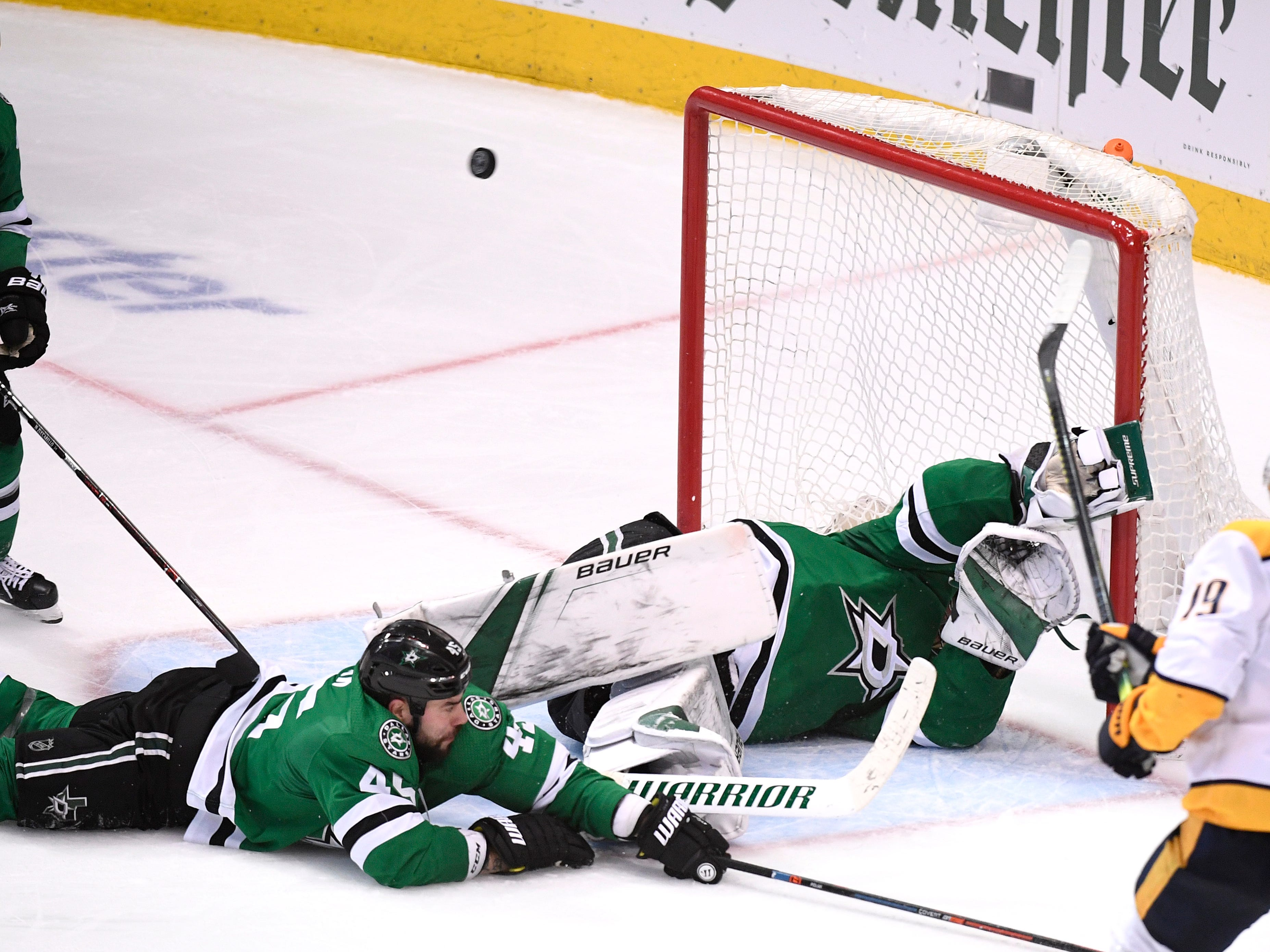 A Predators shot goes wide of the neck as Dallas Stars goaltender Ben Bishop (30) falls to the ice after losing his stick during the third period of the divisional semifinal game at the American Airlines Center in Dallas, Texas, Monday, April 22, 2019.