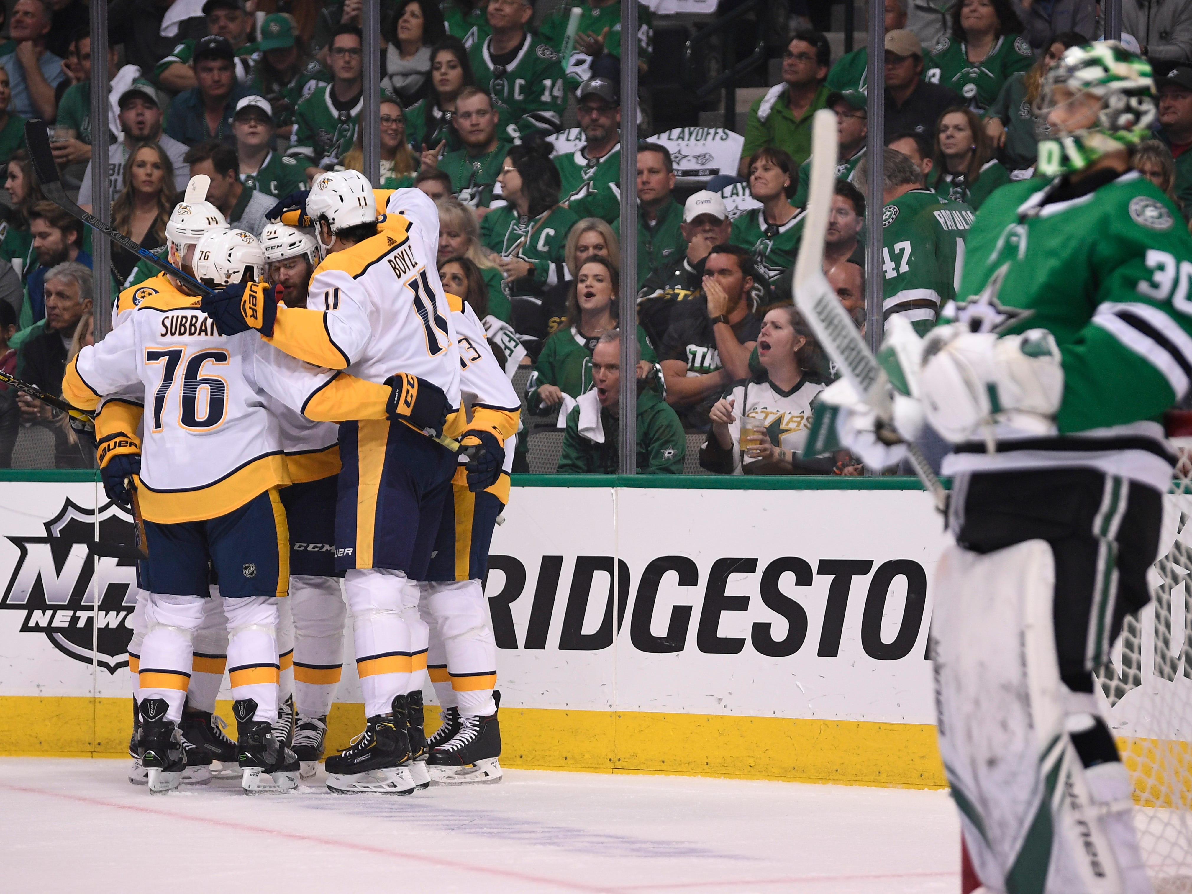 The Predators celebrate the goal by left wing Austin Watson (51) as Dallas Stars goaltender Ben Bishop (30) looks on during the first period of the divisional semifinal game at the American Airlines Center in Dallas, Texas, Monday, April 22, 2019.