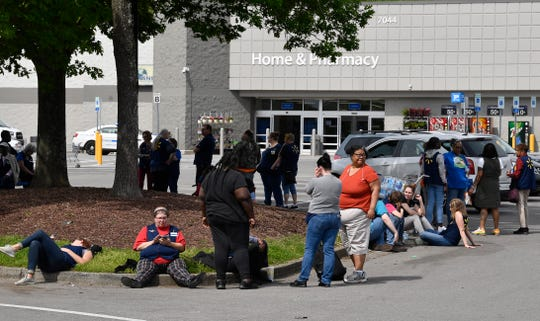Employees wait outside after a gas leak at the Walmart on Charlotte Pike in West Nashville. The fire department said 10 people were suffering from headaches and its AmbuBus responded to the scene on Tuesday, April 23, 2019, in Nashville, Tenn.