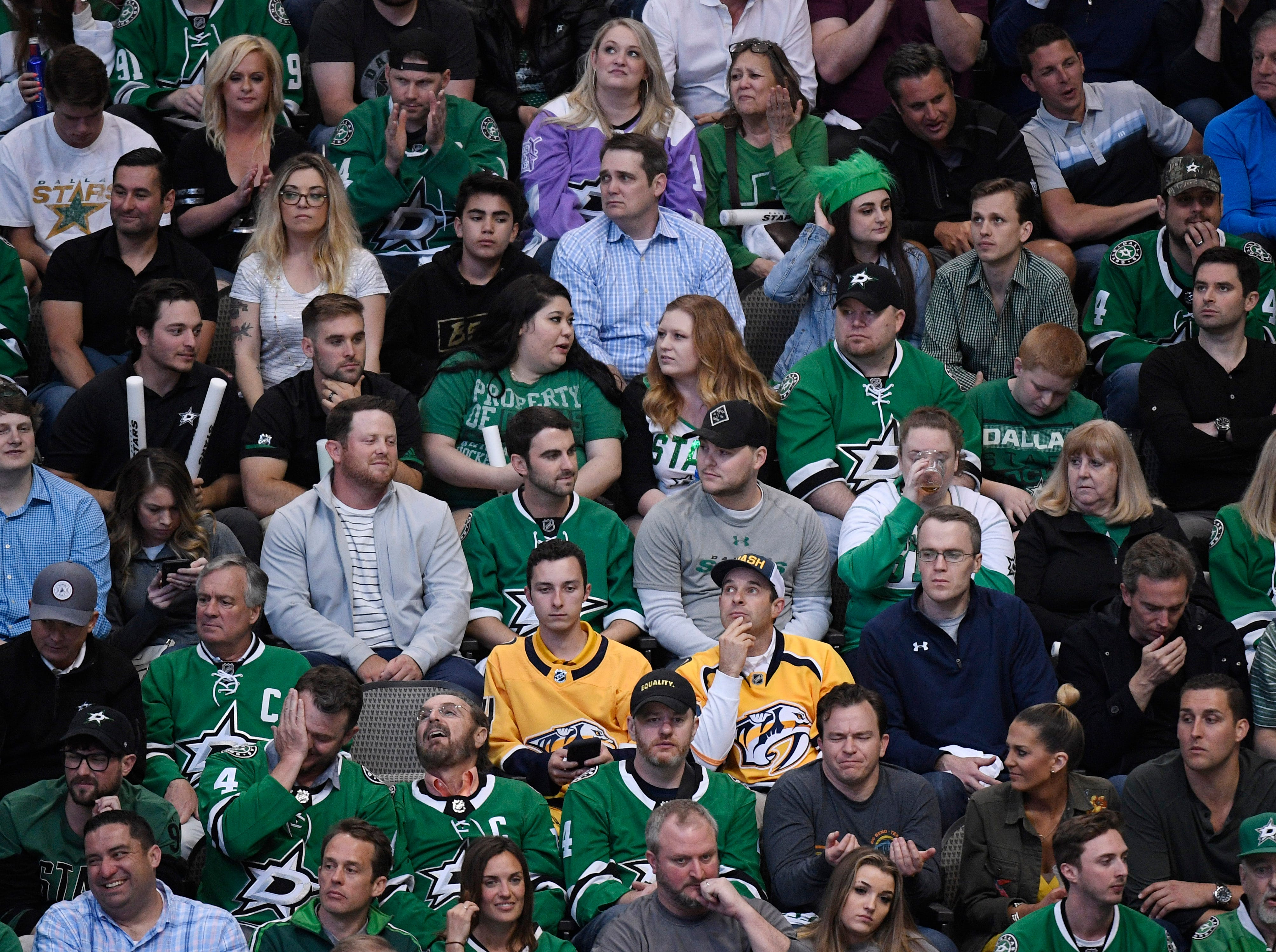 A sea of Dallas Stars fans surround two Nashville Predators fans during the second period of the divisional semifinal game at the American Airlines Center in Dallas, Texas, Monday, April 22, 2019.
