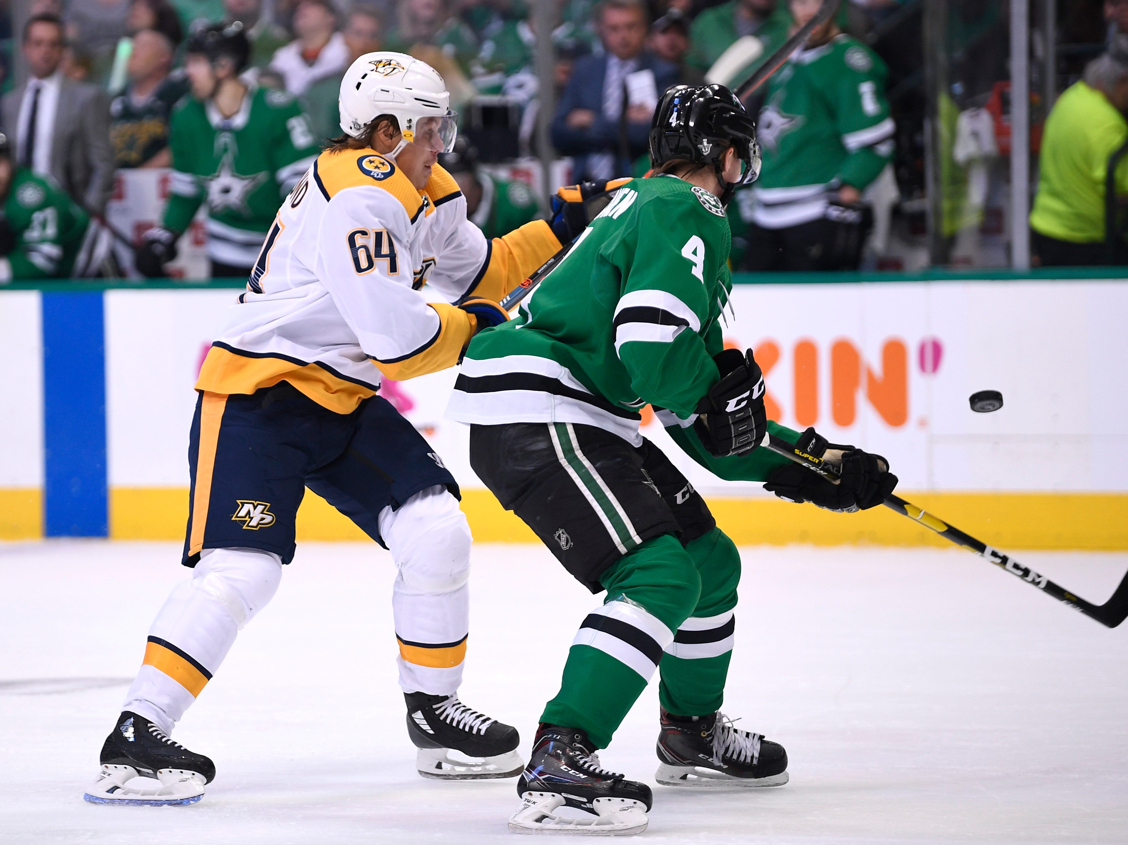 Nashville Predators center Mikael Granlund (64) and Dallas Stars defenseman Miro Heiskanen (4) chase the puck during the first period of the divisional semifinal game at the American Airlines Center in Dallas, Texas, Monday, April 22, 2019.