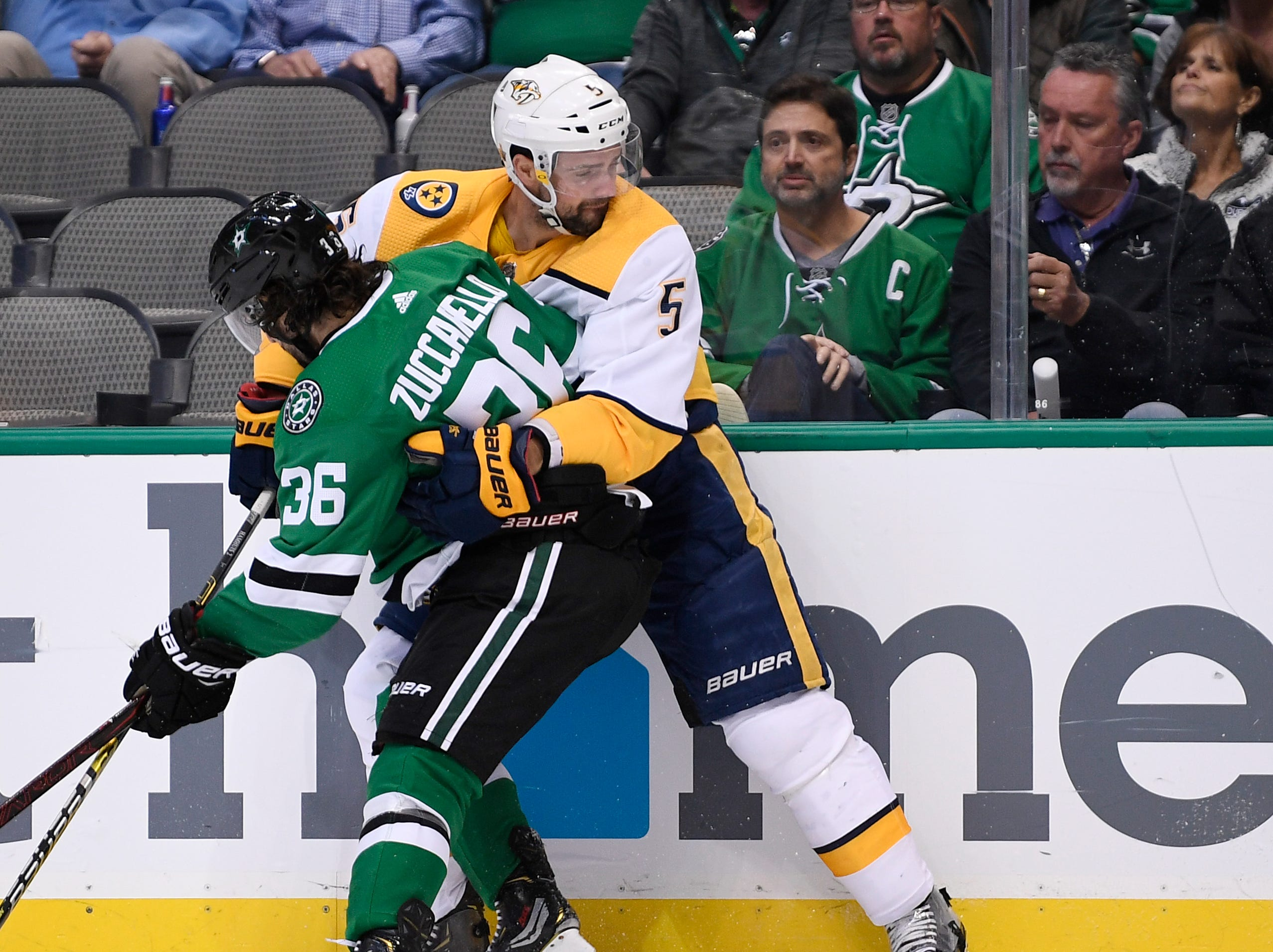 Nashville Predators defenseman Dan Hamhuis (5) and Dallas Stars center Mats Zuccarello (36) battle along the boards during the second period of the divisional semifinal game at the American Airlines Center in Dallas, Texas, Monday, April 22, 2019.