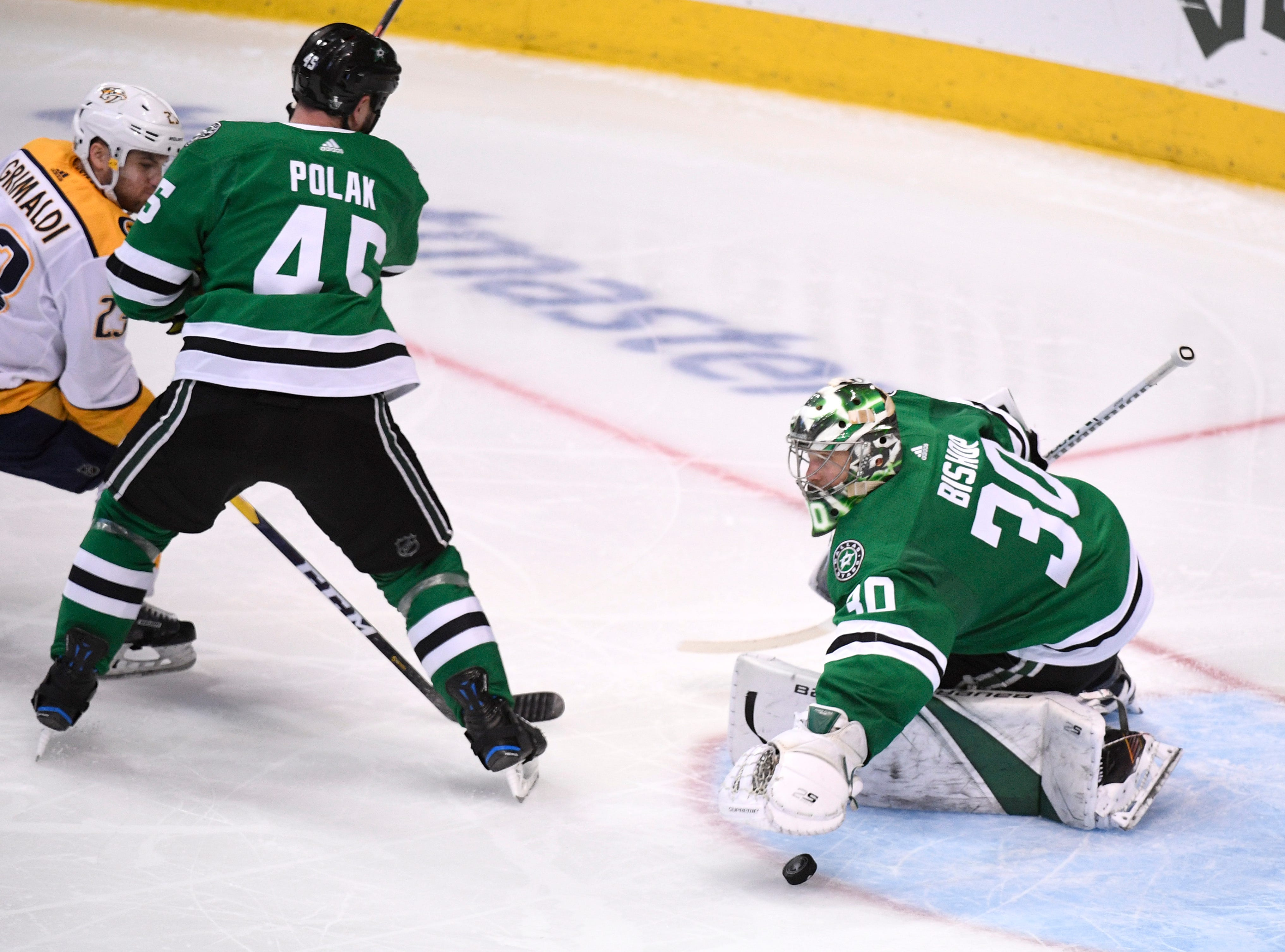 Dallas Stars goaltender Ben Bishop (30) makes a save in front of Nashville Predators center Rocco Grimaldi (23) and Stars defenseman Roman Polak (45) during the third period of the divisional semifinal game at the American Airlines Center in Dallas, Texas, Monday, April 22, 2019.