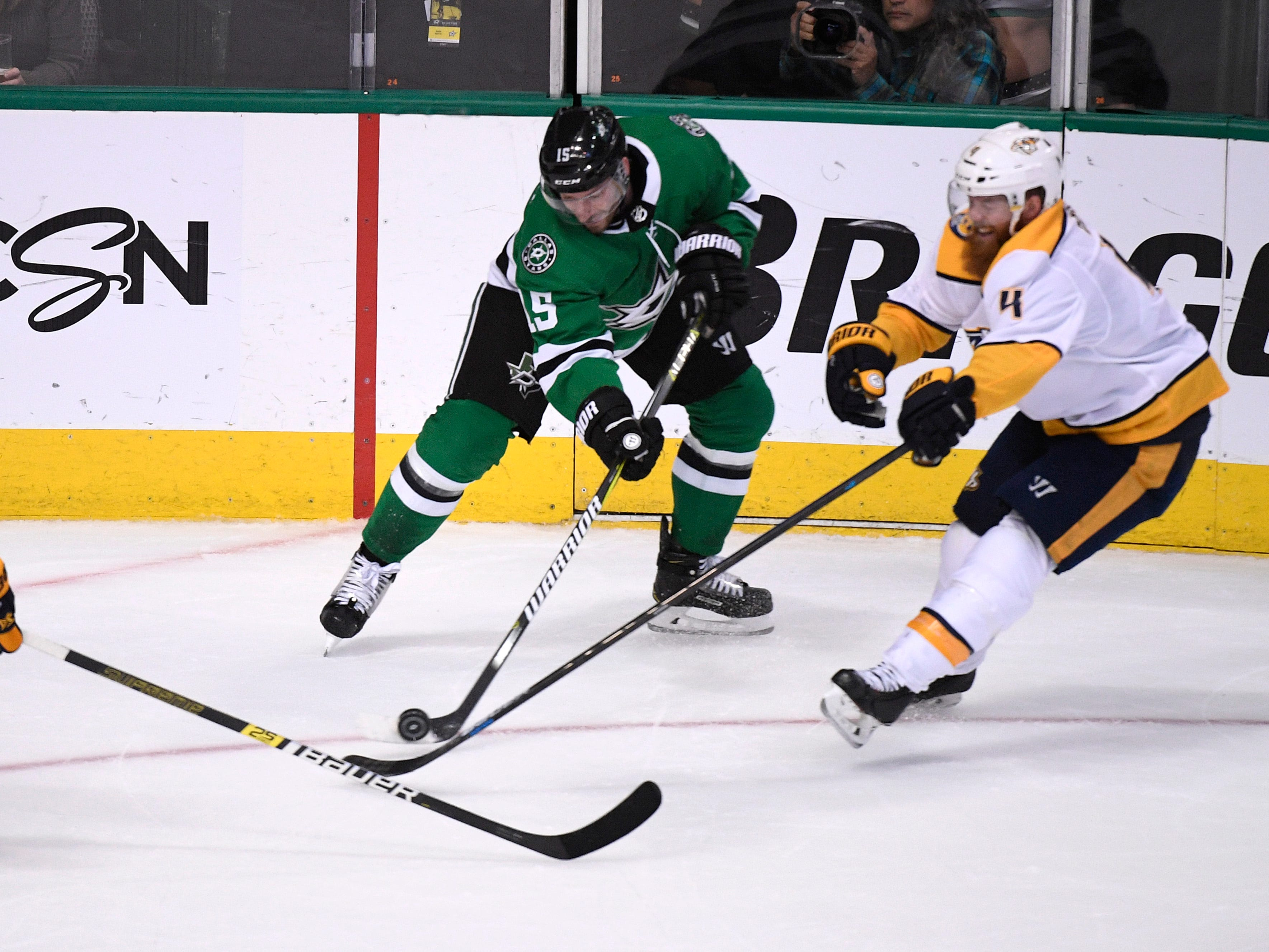 Nashville Predators right wing Craig Smith (15), Dallas Stars left wing Blake Comeau (15) and Predators defenseman Ryan Ellis (4) battle for the puck during the second period of the divisional semifinal game at the American Airlines Center in Dallas, Texas, Monday, April 22, 2019.
