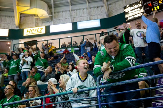 Andrew Sanchez, 10, and Hector Sanchez laugh after the Everblades score their third goal of the second period during Game 6 of the ECHL Kelly Cup Playoffs South Division Semifinals against the Jacksonville Icemen at Hertz Arena on Monday. The Everblades beat the Icemen 5-1.