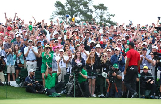 Fans cheer as Tiger Woods leaves the 18th green after winning The Masters golf tournament at Augusta National Golf Club.