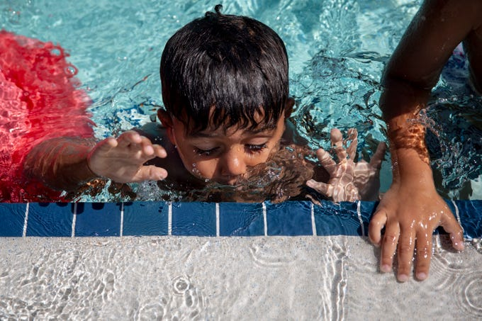 Lingston, center, a preschooler from Sunshine Learning Center, blows bubbles in the water during swim lessons at Eagle Lakes Community Park Aquatic Facility in Naples on Tuesday. The program is part of a grant through NCH Safe and Healthy Children's Coalition of Collier County, funded by the Naples Children and Education Foundation.