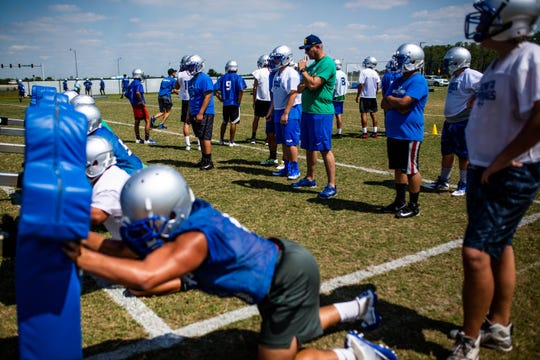 Members of the Bonita Springs High School football team run drills during their first practice on Tuesday, April 23, 2019. This is the first year the school will have a varsity team.