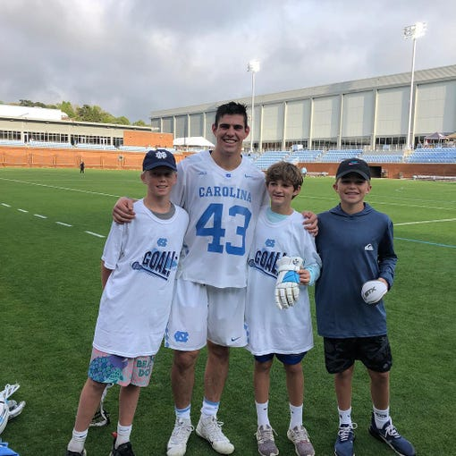 North Carolina lacrosse defenseman and Barron Collier grad Michael Nathan poses with Naples youth players, from left, Corbin Cartwright, Finley Peck and Evan Calkins during a March 2019 visit to Chapel Hill.