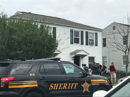 Members of local law enforcement gather outside a Newark home after forcing entry by the Central Ohio Drug Enforcement Task Force on Tuesday, April 23, 2019. Local law enforcement entered the home after receiving several citizens complaints and conducting an investigation.