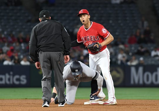 April 22, 2019; Anaheim, CA, USA; Los Angeles Angels shortstop Andrelton Simmons (2) reacts after trying to tag out New York Yankees left fielder Clint Frazier (77) in the twelfth inning at Angel Stadium of Anaheim.