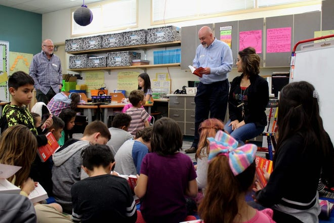 Retired NMSU Professor James Cotter and Ken Binkley, president of the Rio Grande Rotary Club, hand out free dictionaries to third-grade students at University Hills Elementary.