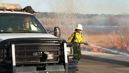 Crews from the New Mexico State Forestry Division fight a grass fire.