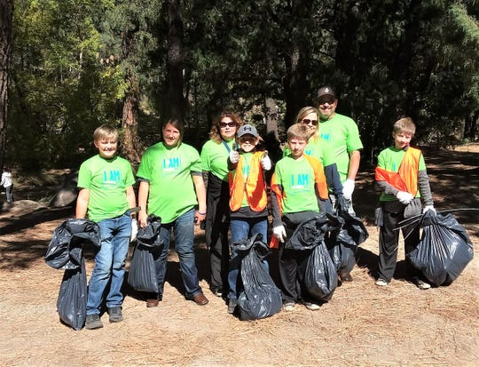 With full trash bags, a team from last year gives the thumbs up.
