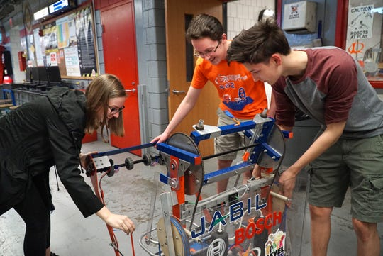 A few of the leaders of Canton High's robotics team take a look at their practice robot on April 22 at the school. From left are: Kristen Gury, Brian Derry, and Aidan Milewski.