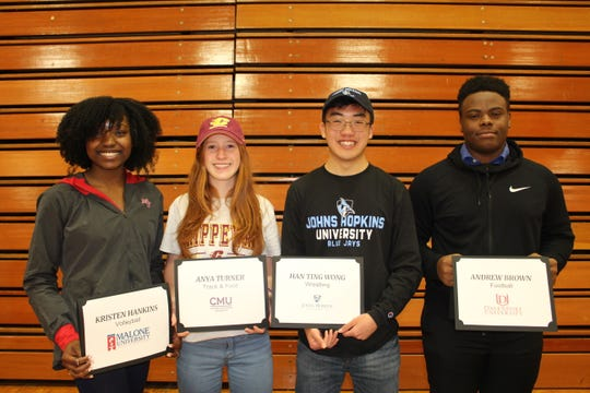 Harrison High's four most recent college signees pose together.
