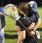 Gulf Breeze head coach Earle McAuley hugs Garrison Story after the Dolphins won the District 1 title on Monday.