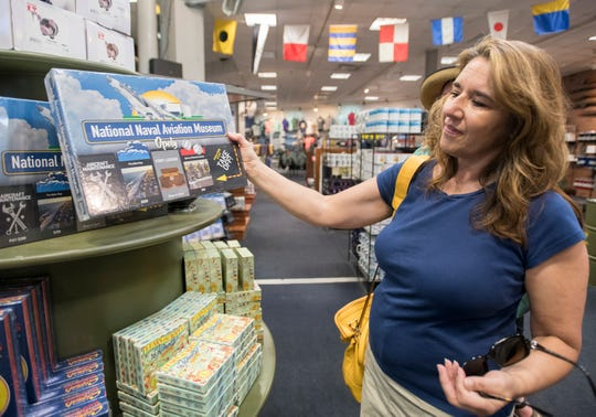 Patty Tighe, of Wheeling, West Virginia, checks out the new National Naval Aviation Museum Opoly game for sale Tuesday at the museum in Pensacola.