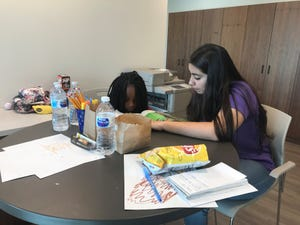 A Grand Canyon University student helps a student with reading at the new Learning Lounge