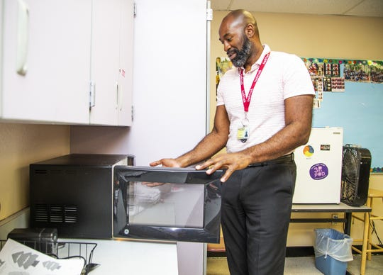 Kareem Neal, the 2019 Arizona Teacher of the Year, shows a microwave he brought from home for his classroom. Neal said one of his special education students needs to use it every day for his meal.