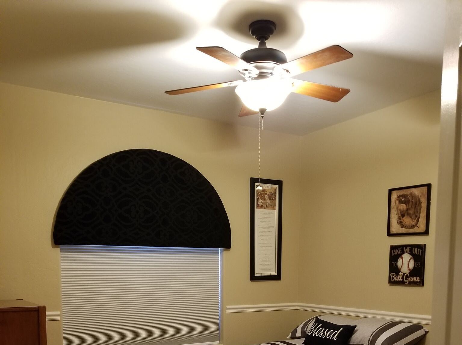 The guest bedroom carries the baseball theme found throughout the LeBoeuf's home. A rounded upholstered cornice frames the window. Cellular blinds, expensive to replace, were spray painted to keep up with changing color themes.