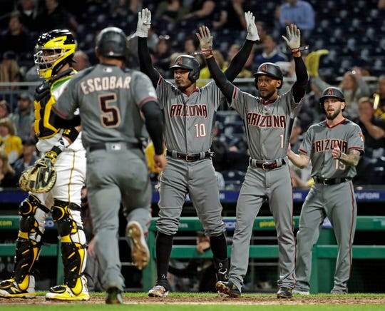 Arizona Diamondbacks' Eduardo Escobar (5) scores the last of three runs on a bases clearing triple by David Peralta during the seventh inning of a baseball game against the Pittsburgh Pirates in Pittsburgh, Monday, April 22, 2019.