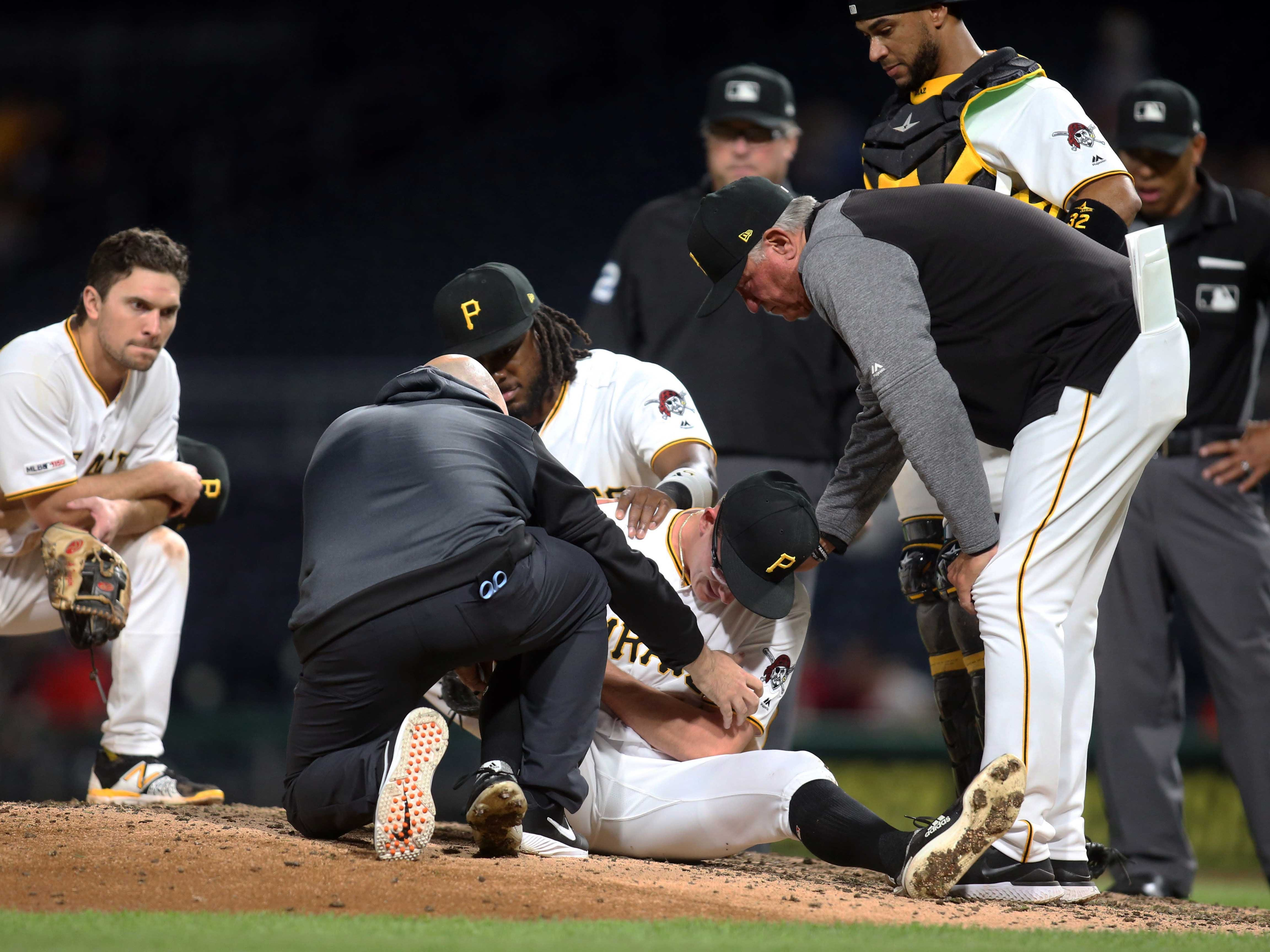 Apr 22, 2019; Pittsburgh, PA, USA;  Pittsburgh Pirates relief pitcher Nick Burdi (center) is attended to by team trainers as teammates and manager Clint Hurdle (13) look on after Burdi suffered an injury while pitching against the Arizona Diamondbacks during the eighth inning at PNC Park.