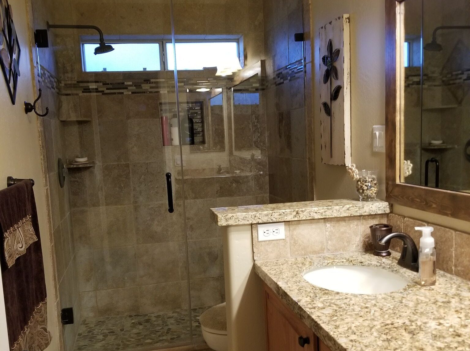Bruce LeBoeuf redid the guest bathroom, including replacing a tub with a shower and encasing the mirror with a wood frame.