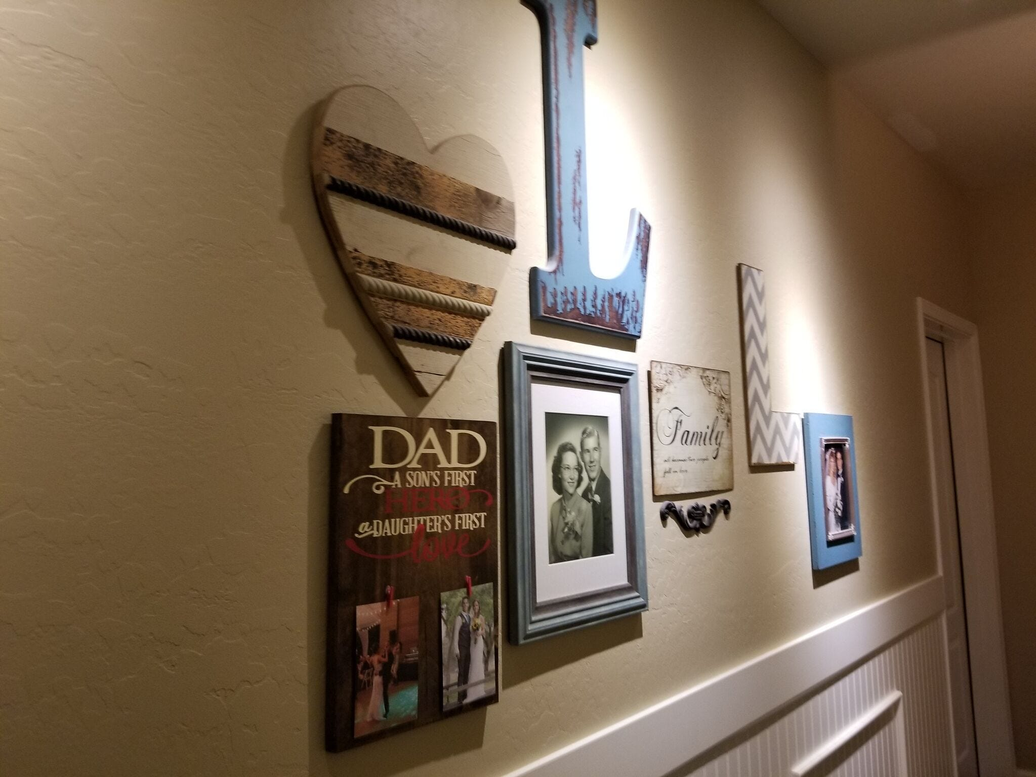 A grouping of family photos hangs on the wall.