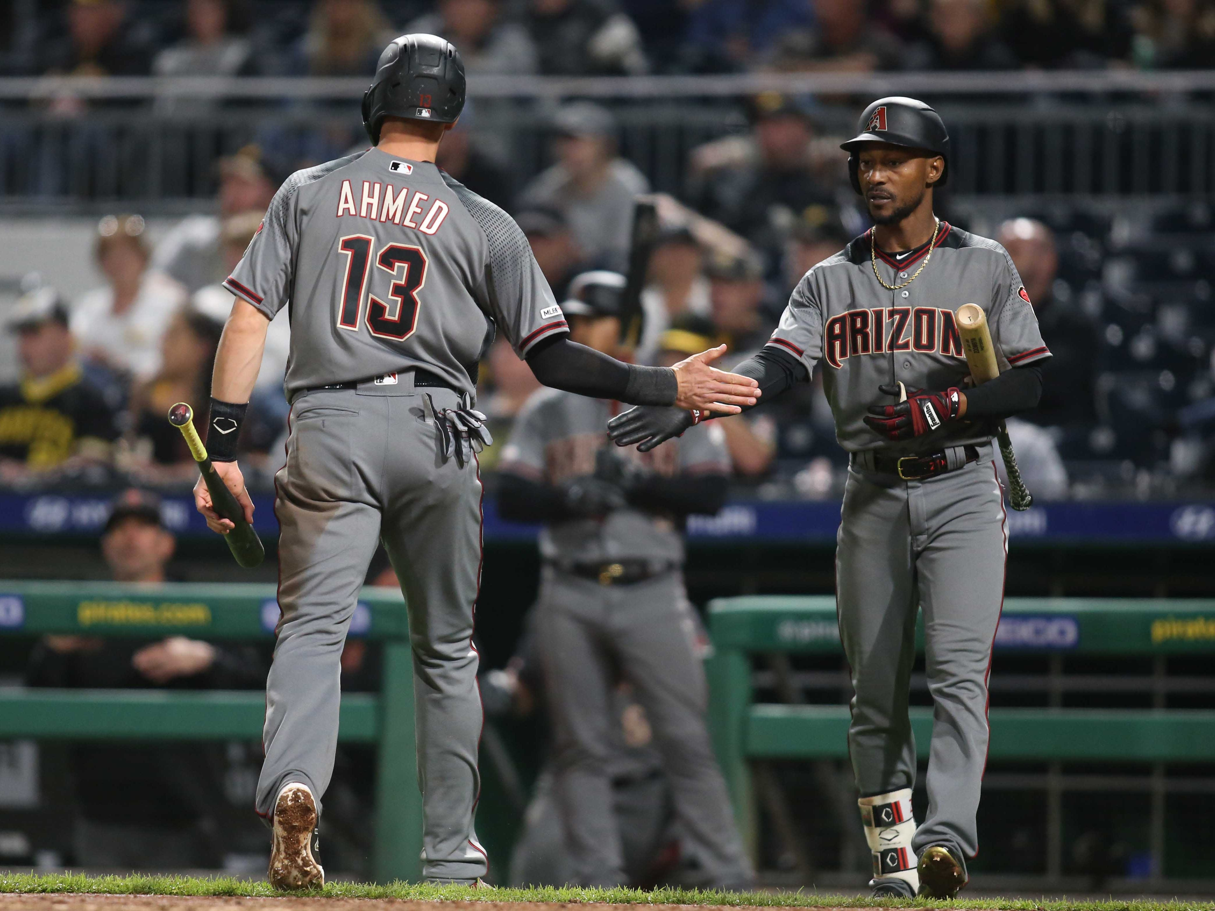 Apr 22, 2019; Pittsburgh, PA, USA;  Arizona Diamondbacks shortstop Nick Ahmed (13) is greeted by center fielder Jarrod Dyson (1) after scoring a run against the Pittsburgh Pirates during the eighth inning at PNC Park.