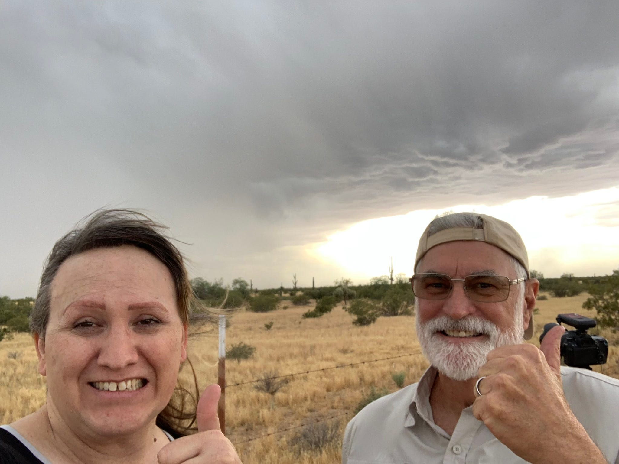 National Weather Service Skywarn Spotter Lori Grace Bailey and friend Dale Cupp smile with their thumbs up in front of storm clouds south of Florence on Tuesday, April 23, 2019.