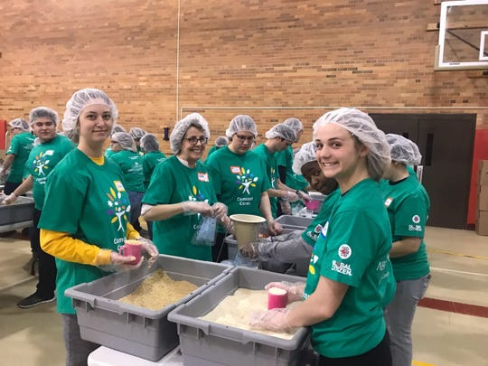 Volunteers pack meals at a Blue Water Feed the World Event.