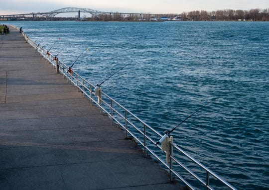 A row of fishing poles hang out over the St. Clair River Monday evening, April 22, 2019 on the boardwalk outside the Municipal Office Center in Port Huron.