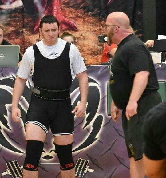 Kennard-Dale powerlifting coach Niko Hulslander, right, talks to Patrick Maloney before a lift at an event in March.
