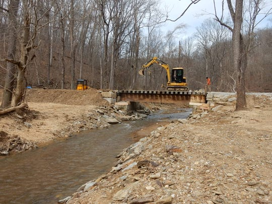 This is the scene of a 30-foot plate bridge after restoration. Rock, silt and debris was cleared. The channel downstream was cleared to lower the water to its pre-flood level. The bridge was retrieved from the stream, cleaned and inspected for reuse, and reinstalled on the abutments. The roadbed on the north and south approaches were rebuilt.