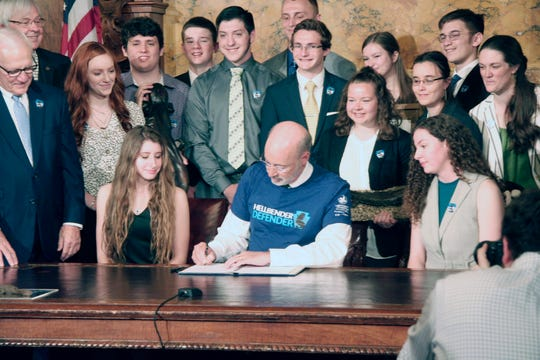 """Wearing a """"HELLBENDER DEFENDER"""" T-shirt, Gov. Tom Wolf signs a bill making the Eastern hellbender salamander the state's amphibian Tuesday, April 23."""