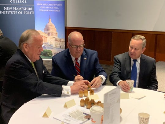 """Maryland Gov. Larry Hogan, center, signs wooden eggs on Tuesday at """"Politics & Eggs,"""" a political breakfast at Saint Anselm College in New Hampshire."""