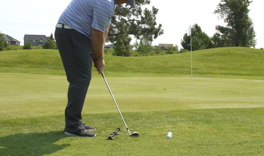 A golfer using the Rimer Short Game Trainer for chipping.