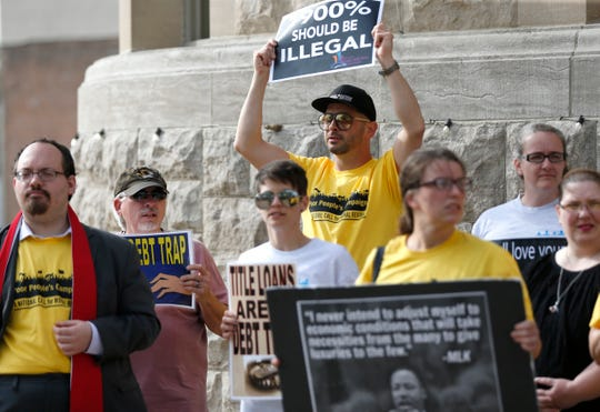 A group from Faith Voices of Southwest Missouri and the Poor People's Campaign protest payday loans outside Historic City Hall before a city council meeting on Monday, April 22, 2019.