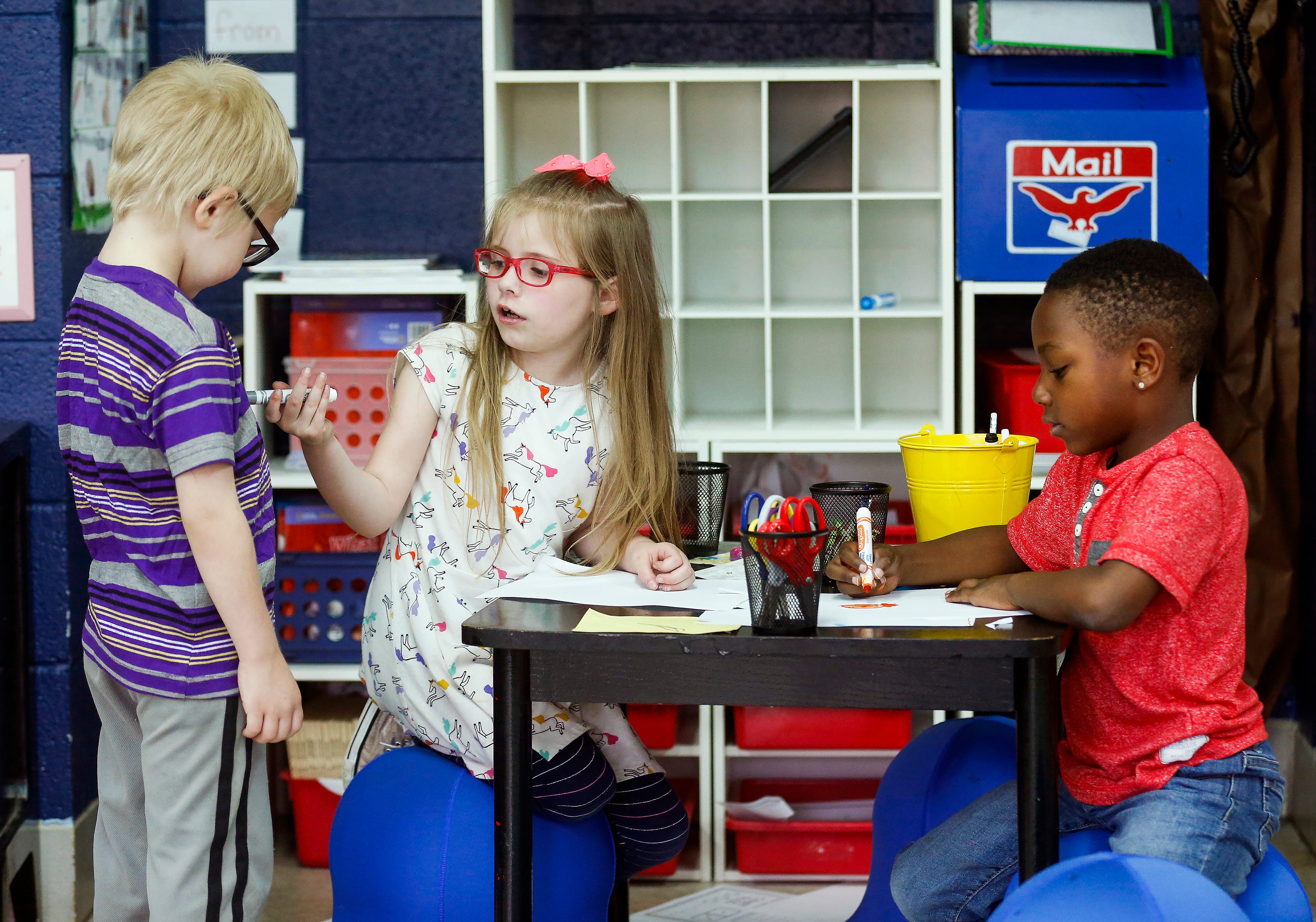 Harley May, center, talks with Calven Rudd, left, as Ayden Nelson does his work in Michelle Pickett's kindergarten class at Cowden Elementary School on Tuesday, April 23, 2019.