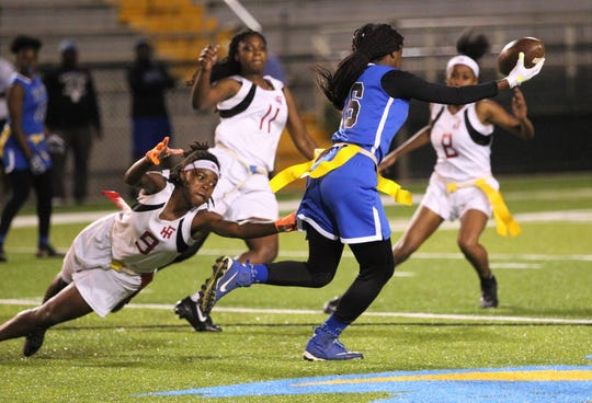 Godby's Essence Nobles escapes Janae Scott's flag-pull attempt to score a 40-yard touchdown as Godby beat Florida High 22-12 in a flag football district semifinal on April 22, 2019.