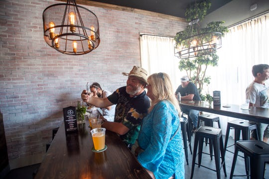 """Steve Haigis (left) and Anna Rossi, both of Port St. Lucie, take a photo Saturday, April 20, 2019, opening day of Bottom's Up Public House in Fort Pierce. """"I think this is pretty cool,"""" Rossi said of the new live music bar. """"There's a lot of outdoor events, but it gets so hot. Tunes on a Saturday in the daytime is great."""""""