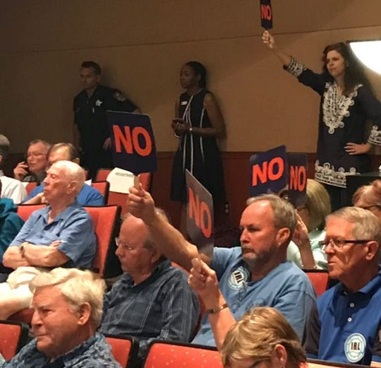 Audience members at the April 23, 2019, Indian River County Commission meeting use signs to voice their opinion of a proposed pipeline under the Indian River Lagoon.