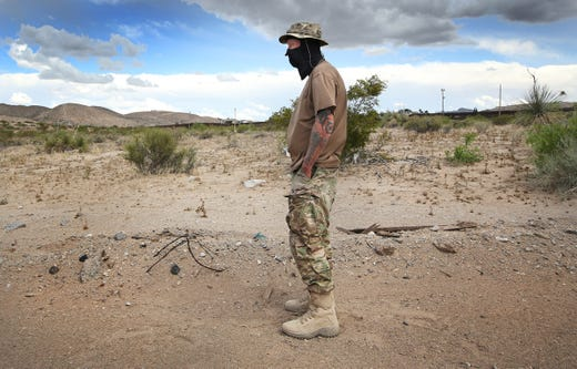 """Viper,"" a member of the United Constitutional Patriots-New Mexico Border Ops, stands dejected after Union Pacific Police evicted the group from their camp in Anapra, New Mexico Tuesday. The group was camping on Union Pacific land."